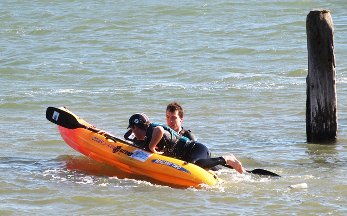 A quick recovery from a capsize as one kayak sets off