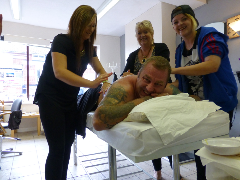 Ian getting waxed by (L-R) Rachael Williamson, Caroline Olive and Rachael Olive