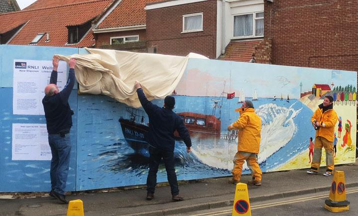 Crew members unveil the mural