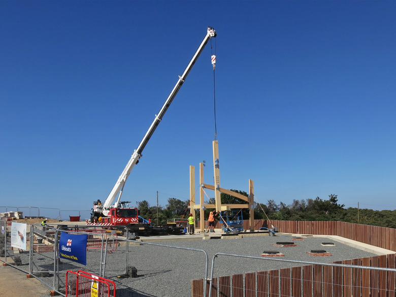 Quick progress lifting frame pieces into position in what will be the workshop area of the building