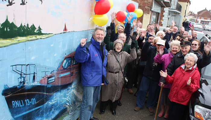 Chairman Peter Rainsford (l) celebrates with Wells Guild members, Swaffham Guild members, Lifeboat crew and supporters