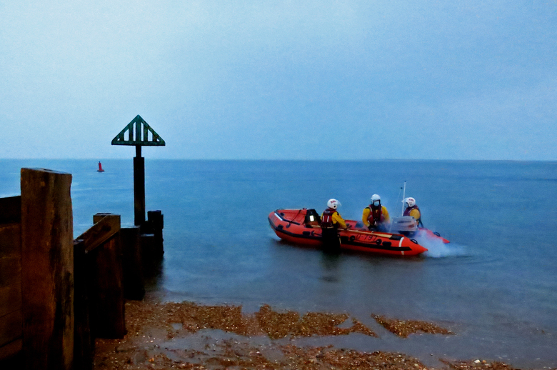 Wells inshore lifeboat launching at daybreak in heavy rain to join the search