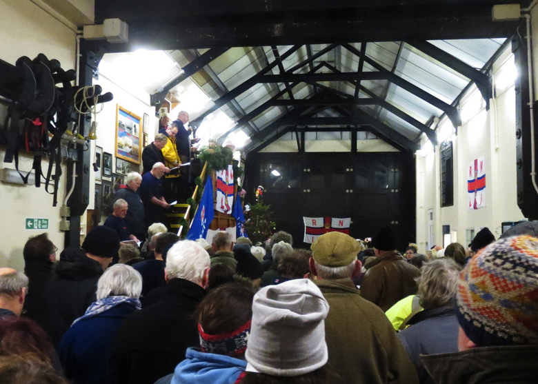 Rev. Neil Woodruff addresses a packed boathouse at the carol service, 14 December 2014