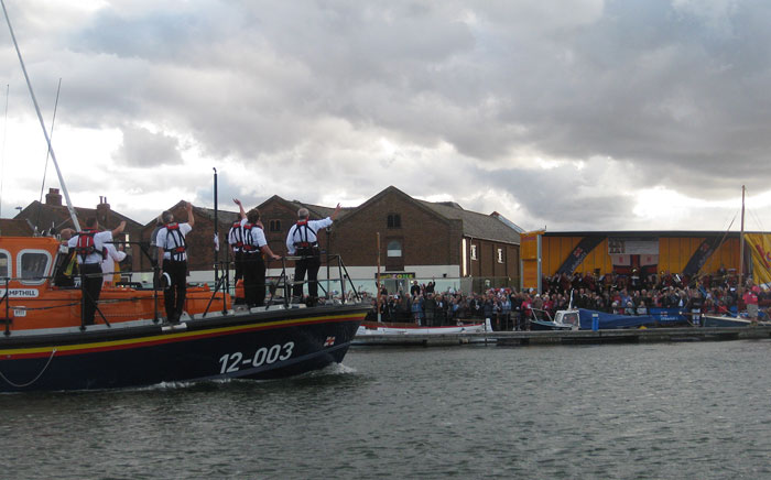 Crew wave to the crowd on the quay after a blustery annual lifeboat service, 10 August 2014
