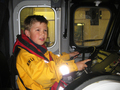 James Dye at the helm of the Mersey class while visiting to donate a welly-full of money collected for the station
