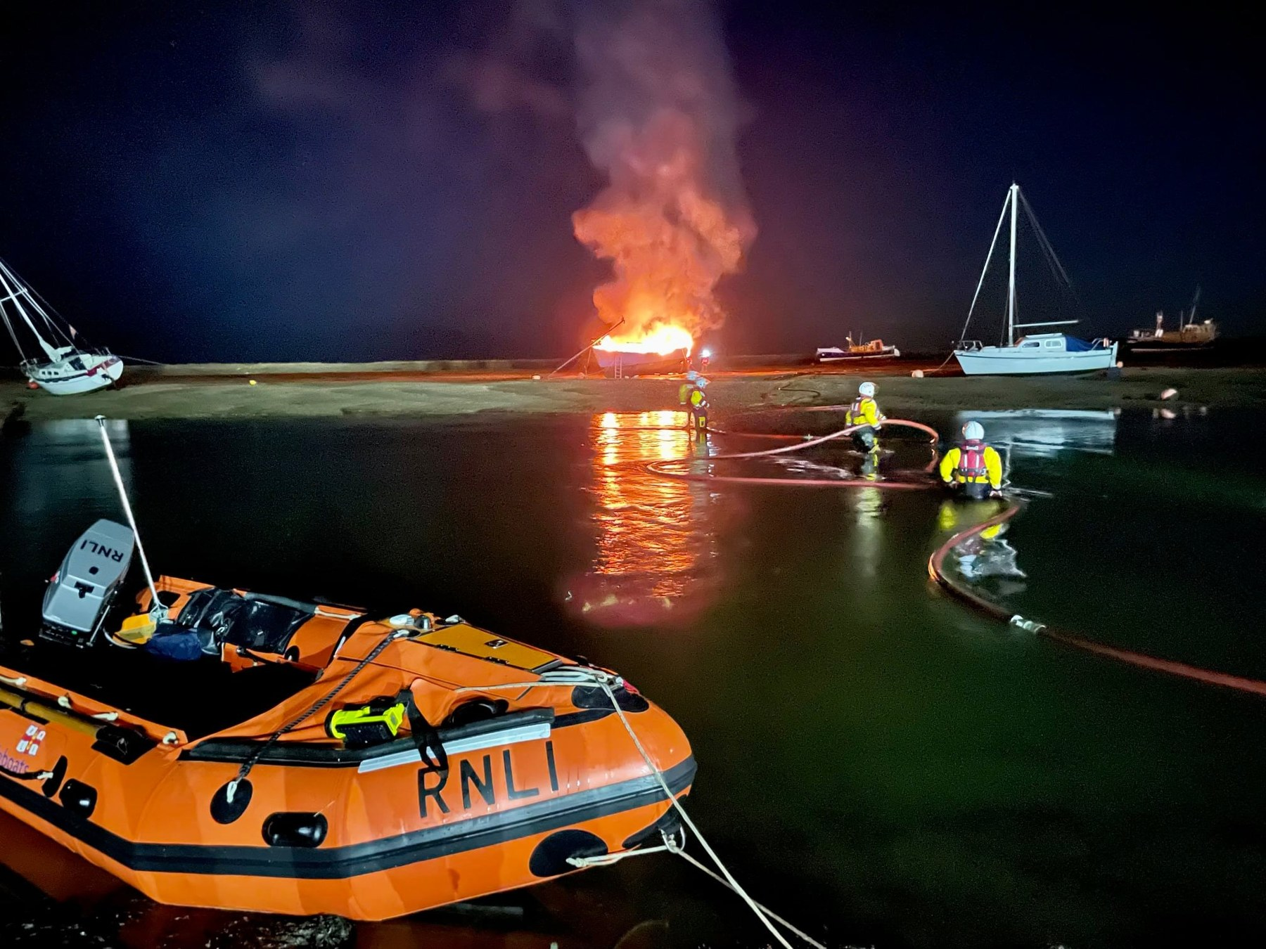 ILB crew assist with feeding fire service hose across the channel, 15/10/21